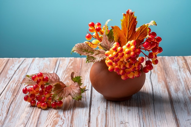 Herbstviburnum im tontopf auf holz