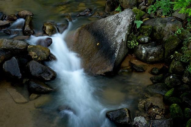 Herbstwasserfallfluss-stromszene. moosige felsen des flusswasserfallherbstes.