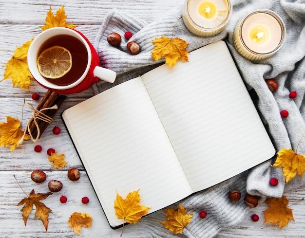 Herbstwohnung lag mit notizbuch, tasse tee und blättern