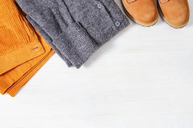Herbstwohnung lag mit warmer kleidung. helle modekleidung für frauen. orangefarbene hose aus cord, wollgrauer strickpullover und bequeme lederstiefel. frauenkleider. draufsicht. flach liegen.