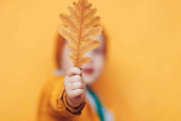 Herbstzeit. lächelndes baby mit gelb verlässt in der hand. saisonale mode. herbstkleidung. kindermode. laubfall. junge in goldener kleidung, orangefarbener hut