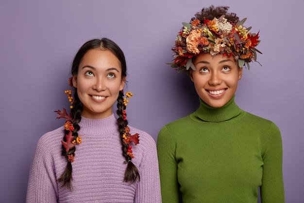 Herbstzeitkonzept. fröhliche junge gemischtrassige frauen in freizeitkleidung, die sich oben konzentrieren, haben ein zahniges lächeln, tragen herbstblätter und beeren im haar, freuen sich über herbstrabatte, posieren im haus