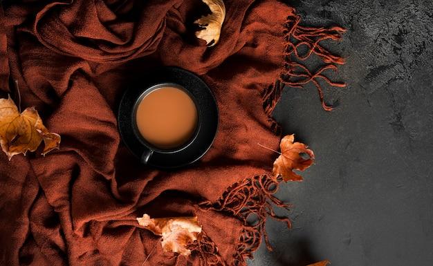 Herbstzusammensetzung. brauner schal, kaffee mit milch, dunkle schokolade mit mandeln und herbstliche ahornblätter. flach liegen. ansicht von oben. foto in hoher qualität