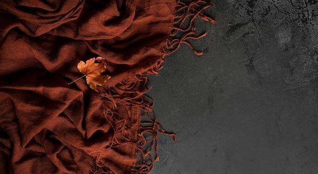 Herbstzusammensetzung. brauner schal und ahornblätter im herbst. flach liegen. ansicht von oben. foto in hoher qualität