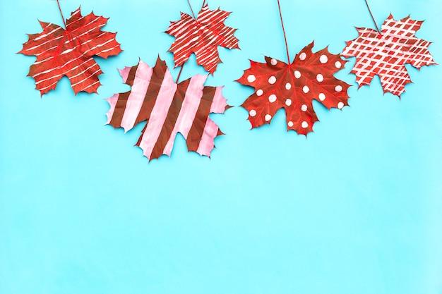 Herbstzusammensetzung des kreativen getrockneten blattahorns gemalt mit gestreiften, tupfen auf hellem hintergrund.
