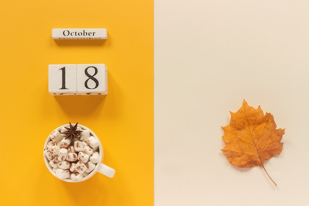 Herbstzusammensetzung. holzkalender oktober, tasse kakao mit marshmallows und gelbem herbstlaub auf gelb-beigem hintergrund. ansicht von oben flach mockup-konzept hallo september.