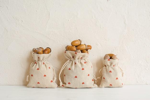 Herbstzusammensetzung mit eicheln in den leinentaschen. herbst, herbst konzept. kopieren sie platz