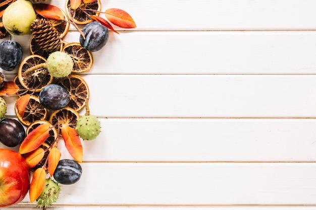 Herbstzusammensetzung mit frucht und blättern auf weißem hölzernem hintergrund