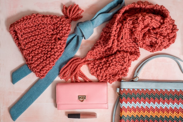 Herbstzusammensetzung mit heller warmer kleidung, filzhut, trockenes gelb verlässt auf rosa konkretem hintergrund. damenaccessoires - tasche, krawatte, brieftasche und lippenstift. herbst-karte
