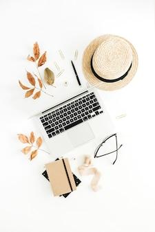 Herbstzusammensetzung mit laptop, trockenem herbstlaub und stroh auf weißem hintergrund. flache lage, ansicht von oben
