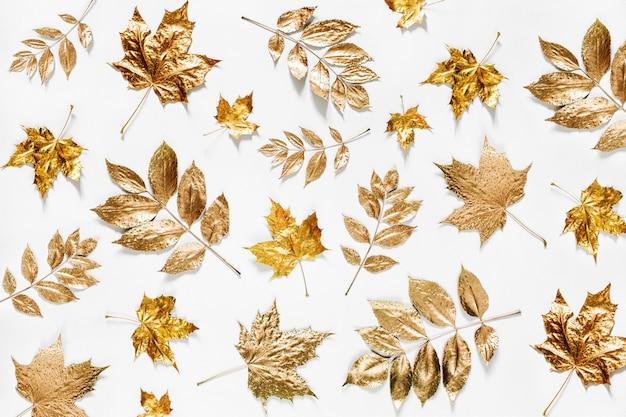 Herbstzusammensetzung. muster aus goldenen herbstblättern auf weißem hintergrund. flache lage, ansicht von oben, kopienraum
