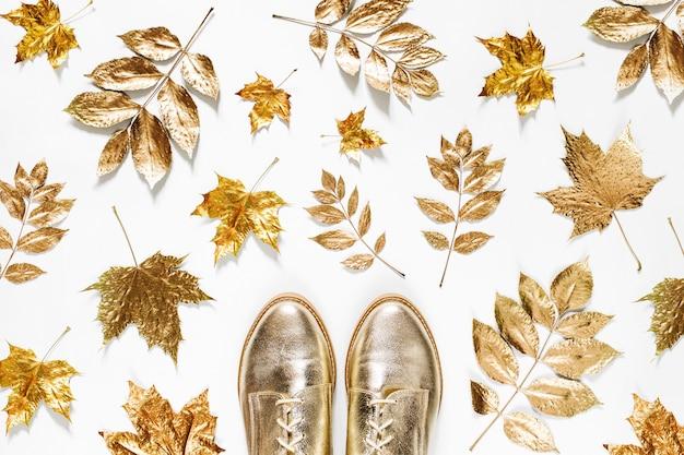 Herbstzusammensetzung. muster aus goldenen herbstblättern und stilvollen schuhen auf weißem hintergrund. flache lage, ansicht von oben