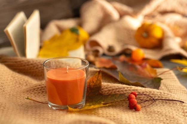 Herbstzusammensetzung. orangefarbene aromakerze auf einem hintergrund aus gefallenen blättern, ebereschen, einer gestrickten decke und einem offenen buch.