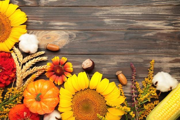 Herbstzusammensetzung. rahmen aus frischen blumen auf braunem holzhintergrund. flache lage, ansicht von oben, kopienraum. erntedank
