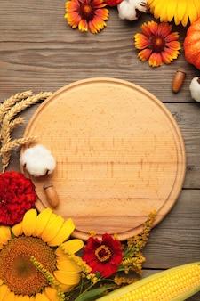 Herbstzusammensetzung. rahmen aus frischen blumen auf grauem holzhintergrund. flache lage, ansicht von oben, kopienraum. erntedank. vertikales foto