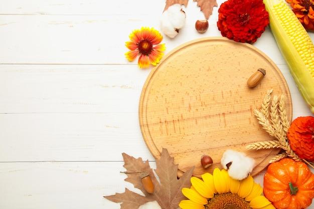Herbstzusammensetzung. rahmen aus frischen blumen auf weißem holzhintergrund. flache lage, ansicht von oben, kopienraum. erntedankfest mit kopienraum.