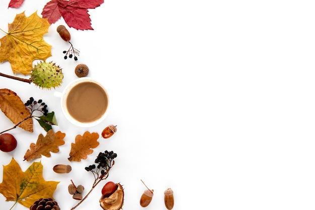 Herbstzusammensetzung. rahmen aus getrockneten blättern, ästen, tannenzapfen, beeren, eicheln und hand mit tasse kaffee auf weißem hintergrund. vorlage mockup herbst, halloween. flach legen, hintergrund kopieren.