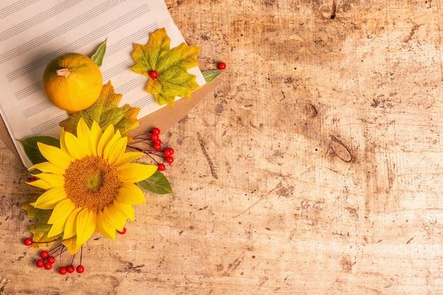 Herbstzusammensetzung. sonnenblume, notizbuch für notizen, rote beeren und kürbisse. festlicher hintergrund für gute laune, flache lage, ansicht von oben