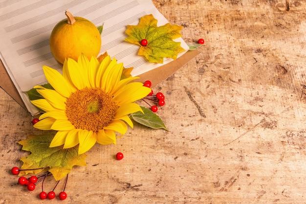Herbstzusammensetzung. sonnenblume, notizbuch für notizen, rote beeren und kürbisse. festlicher hintergrund für gute laune, flache lage, kopienraum