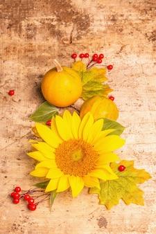 Herbstzusammensetzung. sonnenblumen, rote beeren und kürbisse. festlicher hintergrund für gute laune, flache lage, kopienraum