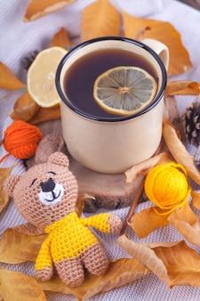Herbstzusammensetzung, tasse tee mit zitrone. sonntag entspannendes und stilllebenkonzept. gestricktes spielzeug, teddy, amigurumi. handgemacht. diy