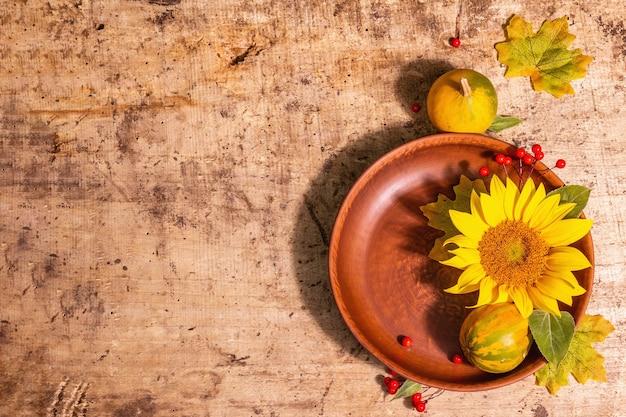 Herbstzusammensetzung. tischdekoration, sonnenblumen, rote beeren und kürbisse. festlicher hintergrund für gute laune, ansicht von oben