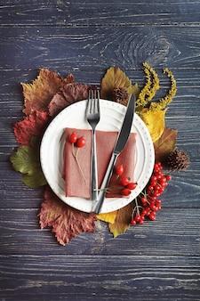 Herbstzusammensetzung von blättern, beeren, teller, messer und gabel auf hölzernem hintergrund. thanksgiving day konzept