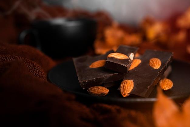 Herbstzusammensetzung. zartbitterschokolade mit mandeln und herbstlichen ahornblättern. flach liegen. ansicht von oben. foto in hoher qualität