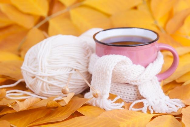 Herbstzusammensetzungstasse tee eingewickelt in einem entspannenden schal saisonmorgentee sonntag