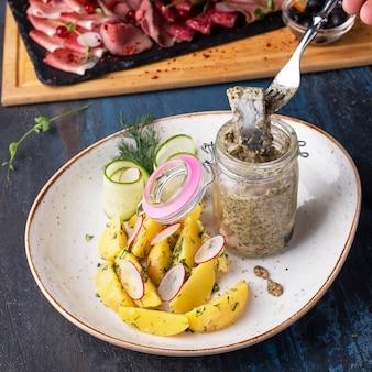 Hering in einem glas mit ofenkartoffeln serviert