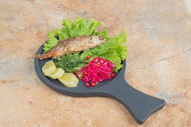 Hering mit salat und rotkohl auf holzbrett