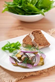 Heringsalat mit eingelegten gurken und zwiebeln