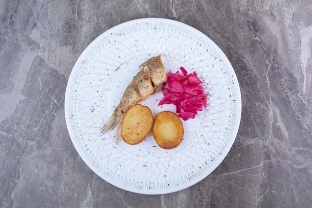 Heringsröllchen, kartoffel und rotkohl auf weißem teller.