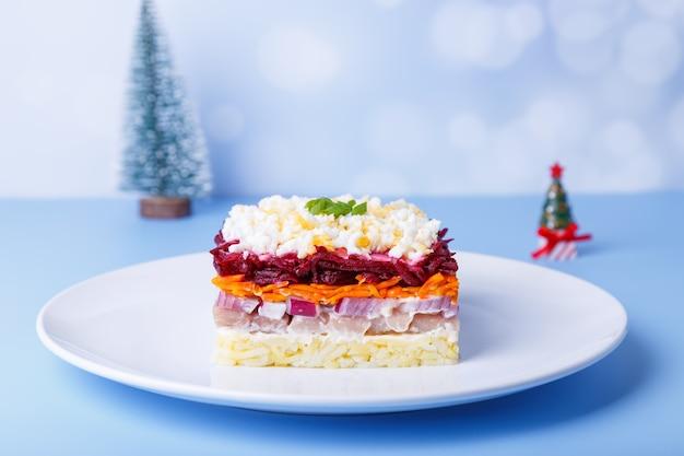 Heringssalat unter einem pelzmantel. traditioneller russischer mehrschichtiger salat aus hering, rüben, kartoffeln, karotten und eiern. nahaufnahme, blauer hintergrund, miniatur-weihnachtsbaum.