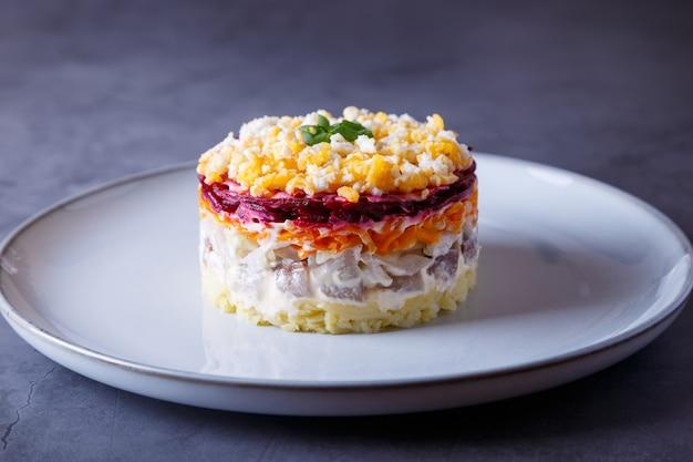 Heringssalat unter einem pelzmantel. traditioneller russischer mehrschichtiger salat aus hering, rüben, kartoffeln, karotten und eiern. nahaufnahme, grauer hintergrund.