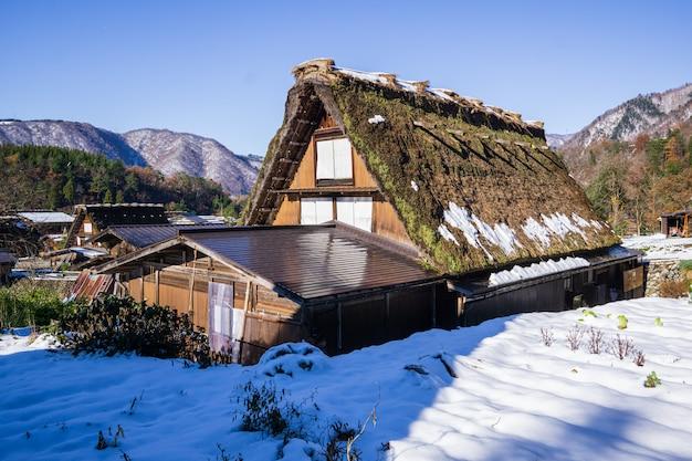 Heritage wooden farmhouse mit schnee umgeben von japans berühmtem dorf.