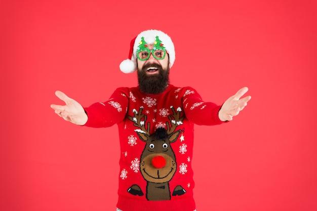 Herkommen. urlaubszubehör. hipster bärtiger mann trägt pullover und hut. pullover mit hirsch. gestrickter pullover. frohes neues jahr. weihnachtsgeist. lustiges outfit. kleidungsgeschäft. festliche kleidung kaufen.