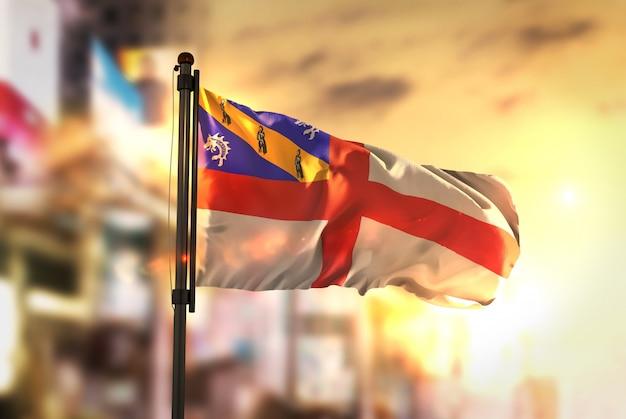 Herm flagge gegen stadt verschwommen hintergrund bei sonnenaufgang hintergrundbeleuchtung