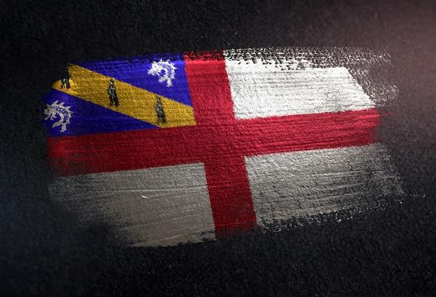 Herm-flagge gemacht von der metallischen bürsten-farbe auf dunkler wand des schmutzes