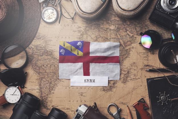 Herm-flagge zwischen dem zubehör des reisenden auf alter weinlese-karte. obenliegender schuss