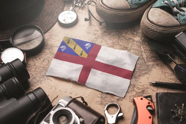 Herm-flagge zwischen dem zubehör des reisenden auf alter weinlese-karte. touristisches bestimmungsort-konzept.