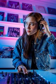 Hermosa mujer dj alegre disfrutando de escuchar musica por sus auriculares mientras mezcla musica