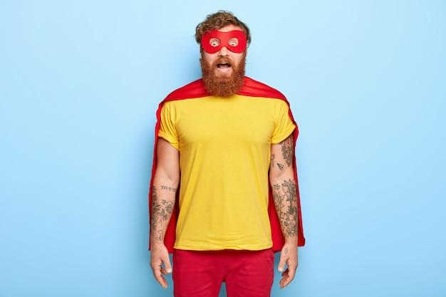 Heroischer mann mit verblüfftem, verängstigtem gesichtsausdruck starrt durch die rote maske