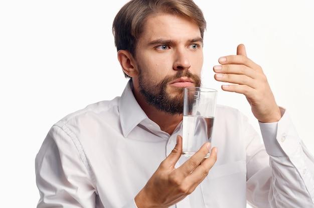 Herr in einem weißen hemd hält ein glas wasser in seiner hand auf einem hellen hintergrund.