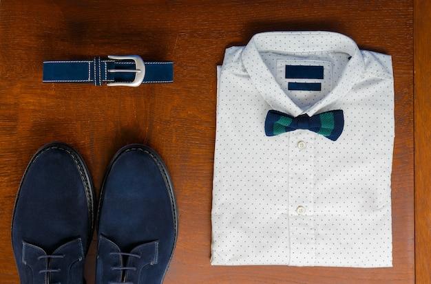 Herren-outfits, weißes tupfenhemd mit fliege, blauem gürtel und schuhen auf braunem hintergrund. hochzeitszubehör für herren.