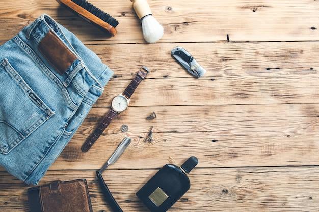 Herrenaccessoires mit jeans und parfüm auf dem schreibtisch