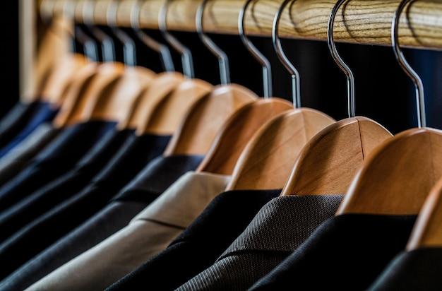Herrenanzüge in verschiedenen farben hängen am kleiderbügel in einem bekleidungsgeschäft, nahaufnahme. herrenhemden, anzug hängt am gestell.