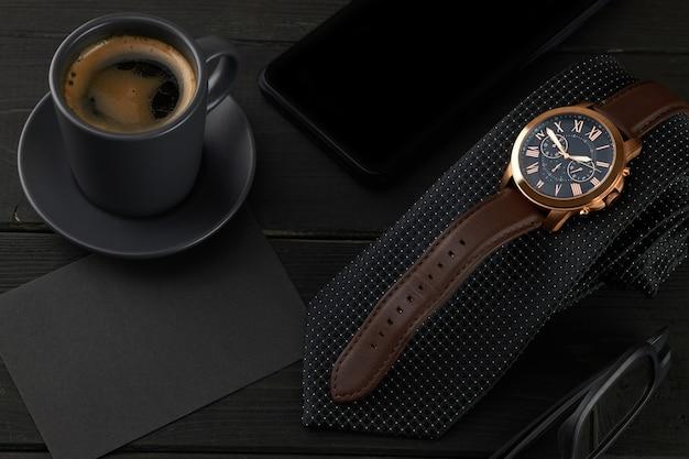 Herrenarmbanduhr auf schwarzer krawatte, einer heißen tasse kaffee und einem smartphone auf einem holztisch. schwarzer umschlag mit platz für text.