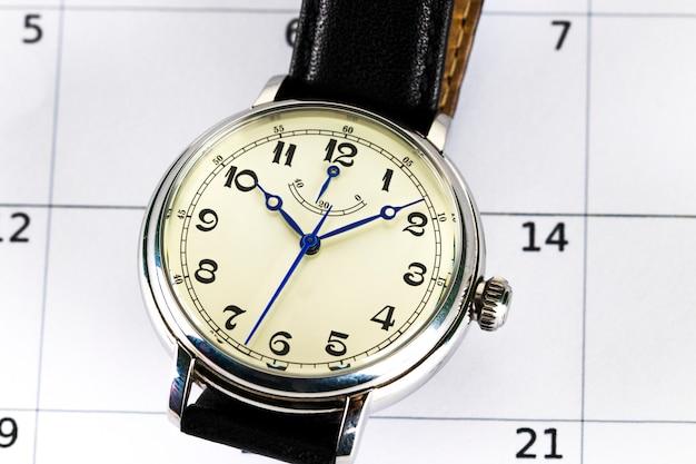 Herrenarmbanduhr und kalender. konzept von datum und uhrzeit