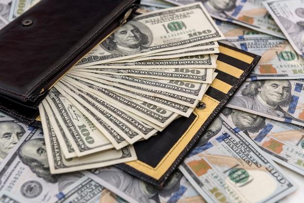 Herrengeldbörse aus dunklem leder voller dollarnoten als finanzieller hintergrund, sparkonzept